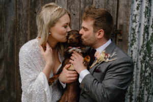 Bride and groom kiss their cute sausage dog who is wearing a tiny wedding tux at East Yorkshire Barns