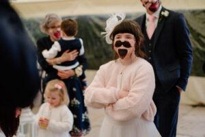 flower girl wearing funny face mask at saltmarshe hall wedding
